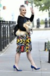 Kelly Osbourne carries her dog on the way out of her apartment rocking a colorful print skirt and lavendar mohawk buns in NYC