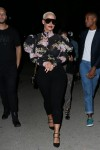 Amber Rose pairs her feminine yet see-through blouse with a metal grill as she arrives at ASAP Rocky's Guess Club in Los Angeles