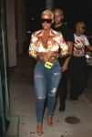 Amber Rose arrives at Catch restaurant wearing ripped denim, bright print silk blouse and dark sunglasses