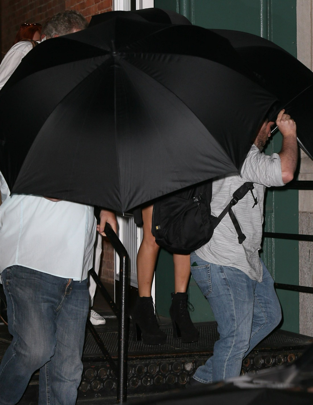 Taylor Swift and parents use umbrellas to hide themselves as they leave out the backdoor of her apartment