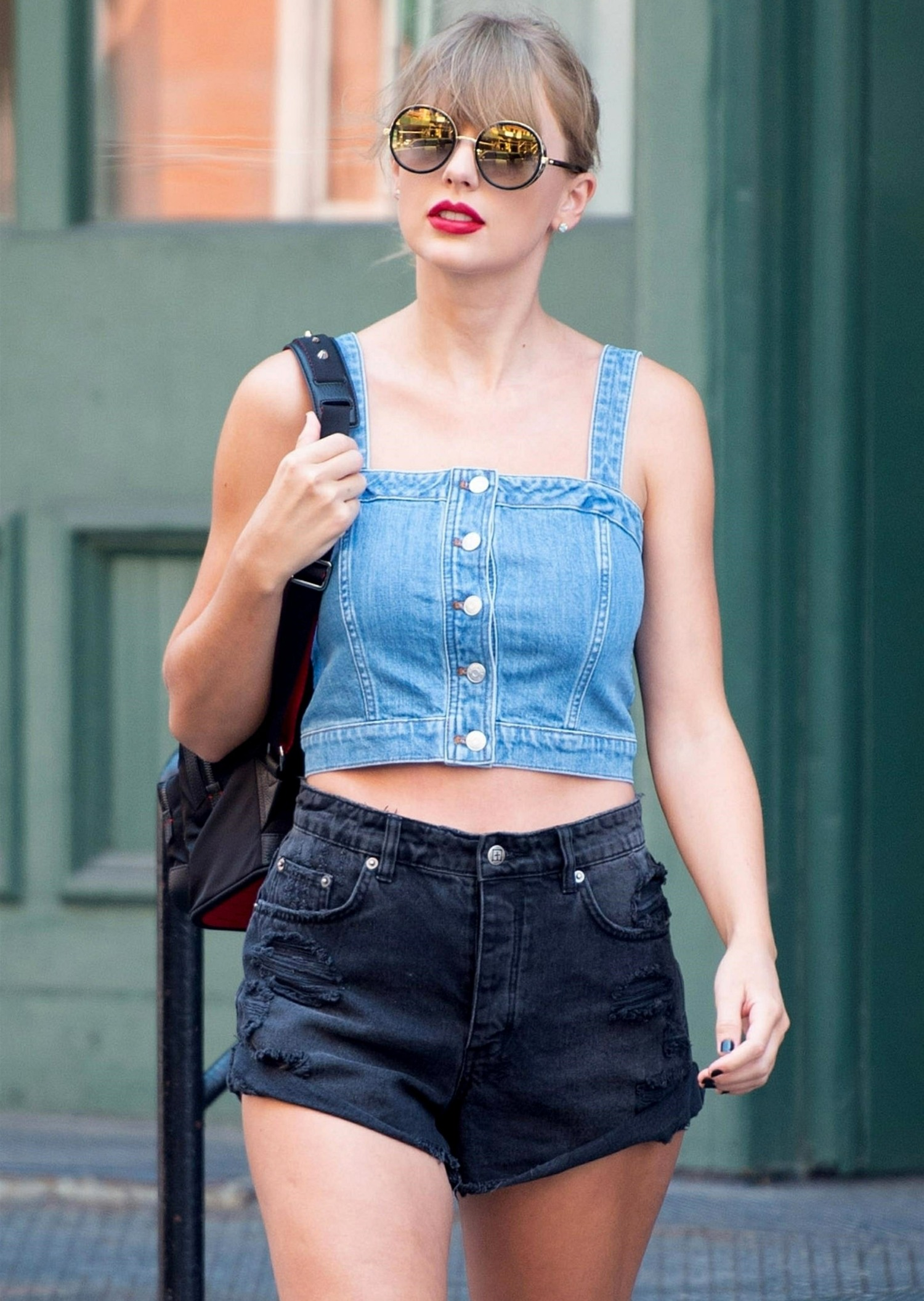 Taylor Swift steps out of her apartment showing off her legs in a pair of short shorts