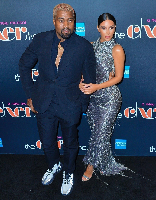 Kim Kardashian and Kanye West pose on the black carpet during Cher's opening night