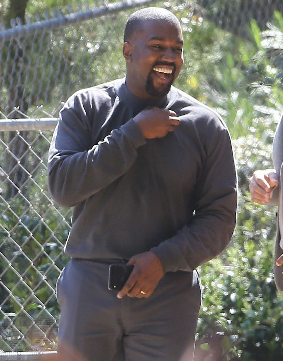 Kanye West looks cheerful as he chats with friends after his church service