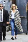 Elizabeth Banks arrives for an appearance on Jimmy Kimmel Live! wearing a long black and white checked coat