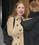 Chelsea Clinton seen smiling in a blue dress and a trench coat