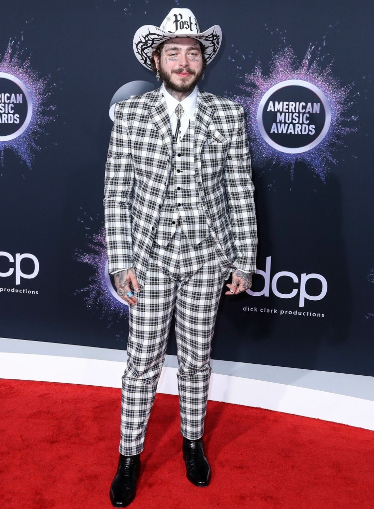 Rapper Post Malone wearing a Charbel Zoe dress arrives at the 2019 American Music Awards held at Microsoft Theatre L.A. Live on November 24, 2019 in Los Angeles, California, United States.
