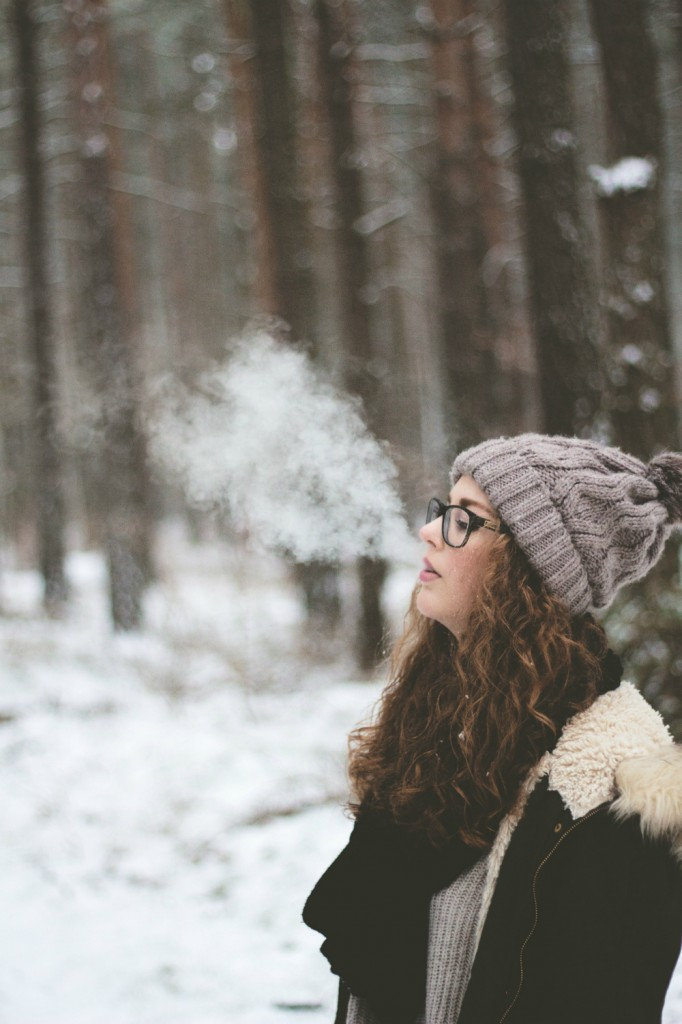 woman-standing-and-smoking-on-snow-covered-forest-2182190