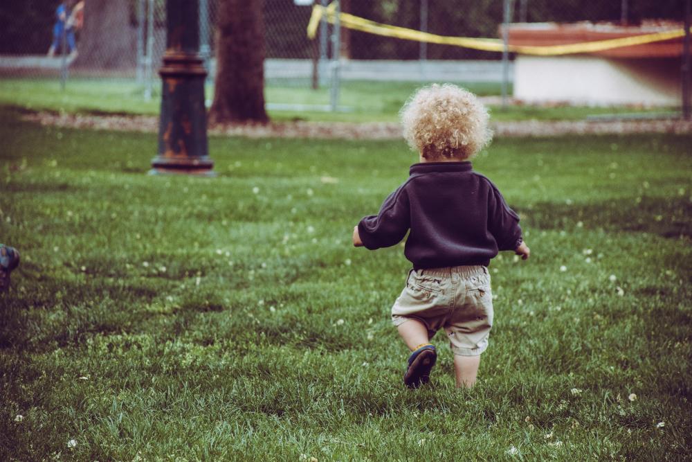 boy-wearing-marrone-pantaloncini-standing-on-green-grass-1073091
