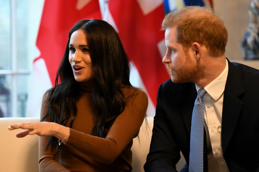 Britain's Prince Harry, Duke of Sussex (R) listens as Meghan, Duchess of Sussex speaks during their visit to Canada House in thanks for the warm Canadian hospitality and support they received during their recent stay in Canada,  in London on January 7, 202