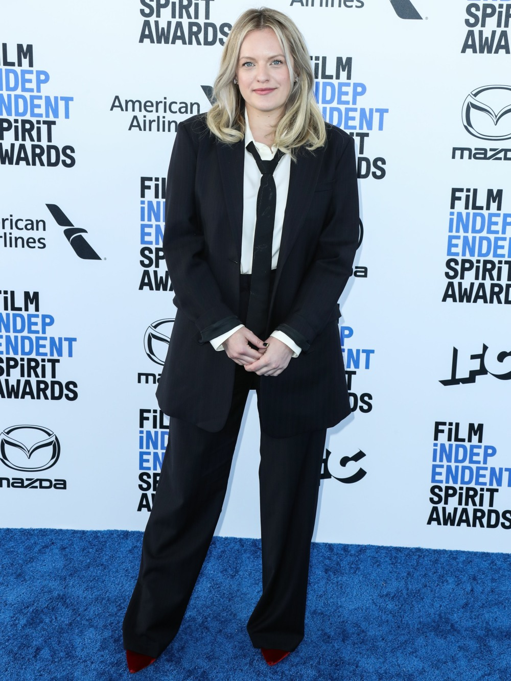 Actress Elisabeth Moss wearing a Co suit, Theory blouse, Jimmy Choo shoes, and Harry Kotlar earrings...