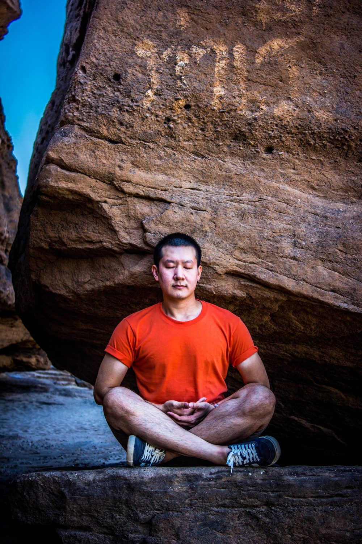 man-meditating-under-rock-1241348