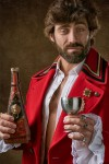 man-holding-red-and-black-bottle-3115350