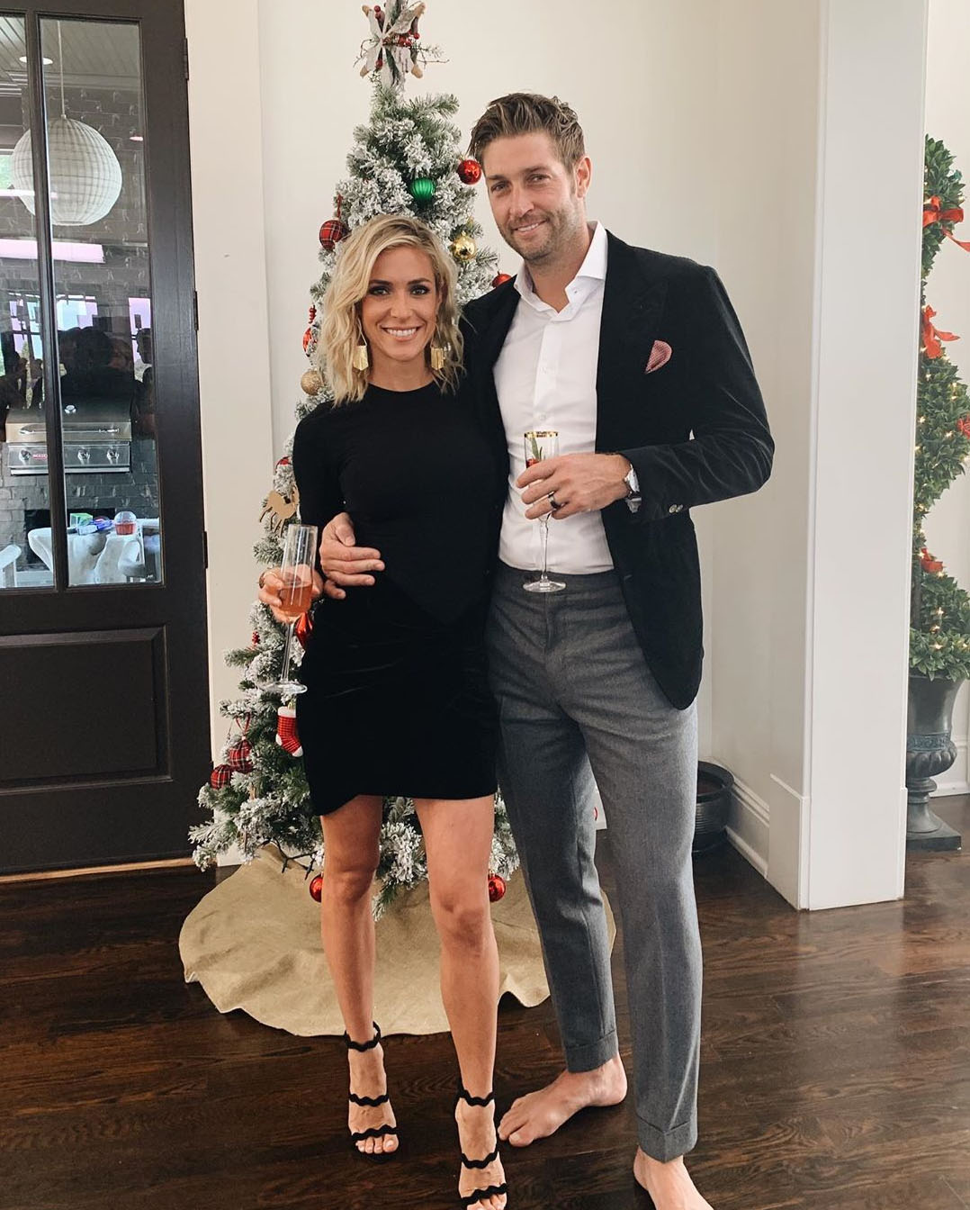 Kristin Cavallari and Jay Cutler in front of a Christmas tree. Jay is barefoot for some reason.