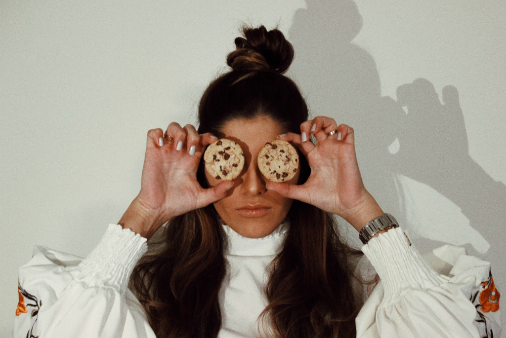 woman-covering-eyes-with-two-chocolate-chip-cookies-1550918