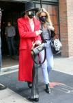Miley Cyrus rocks a red trench coat as she steps out of her hotel