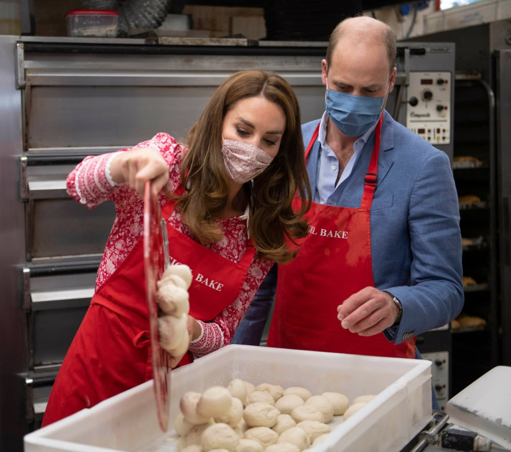 Britain's Prince William, Duke of Cambridge (R) watches as his wife Britain's Catherine, Duchess of Cambridge pours a tray of dough into a container as they help make beigels during a visit to Beigel Bake Brick Lane Bakery in east London on September 15,
