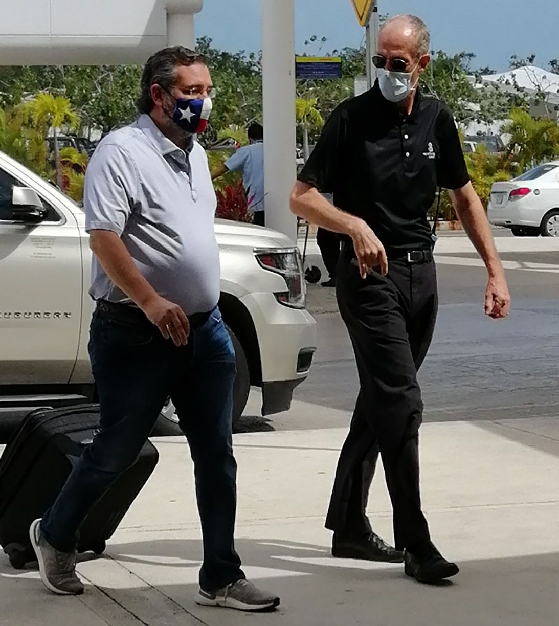 Ted Cruz wears Texas flag mask as he arrives at CanCun airport this morning ahead of flight back to Texas hours after landing in Mexico