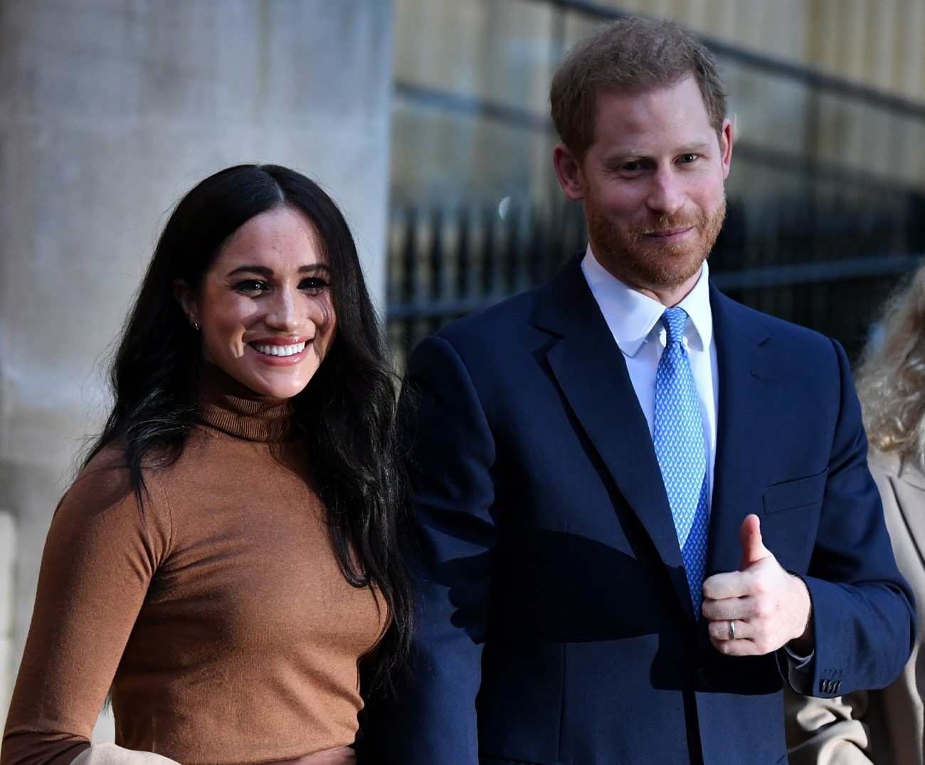 Britain's Prince Harry, Duke of Sussex (C) and Meghan, Duchess of Sussex (L) stand with Canada's High Commissioner for Canada in the United Kingdom, Janice Charette, as they leave after their visit to Canada House in thanks for the warm Canadian hospitalit