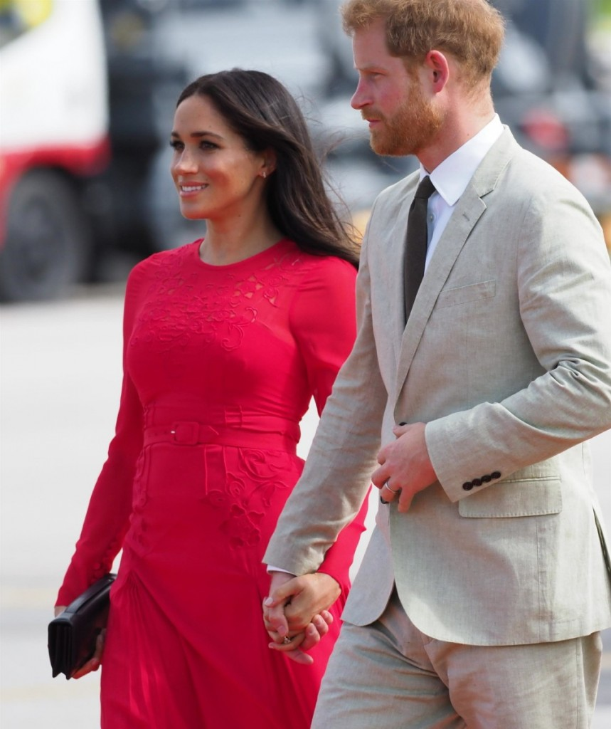 A windswept Prince Harry and Mehgan Markole arrive in Tonga
