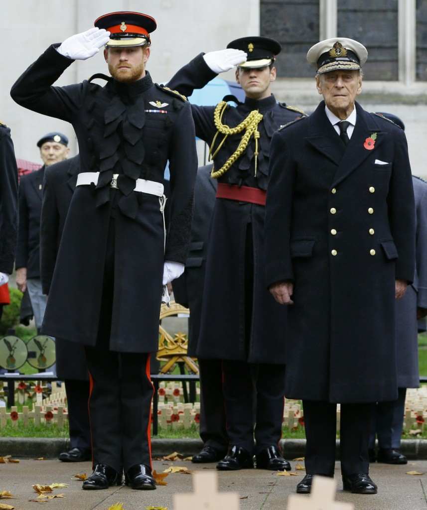 Britain's Prince Harry, left, salutes next to The Duke of Edinburgh during a visit to the Field of Remembrance at Westminster Abbey in London, Thursday, Nov. 5, 2015. The Duke of Edinburgh and Prince Harry each placed a Cross of Remembrance for Unknown Br