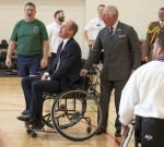 The Duke of Cambridge and Prince Charles react following his failed attempt to throw a basketball in...