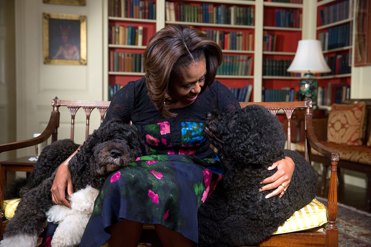 First Lady Michelle Obama, seated with Obama family pets Bo and Sunny