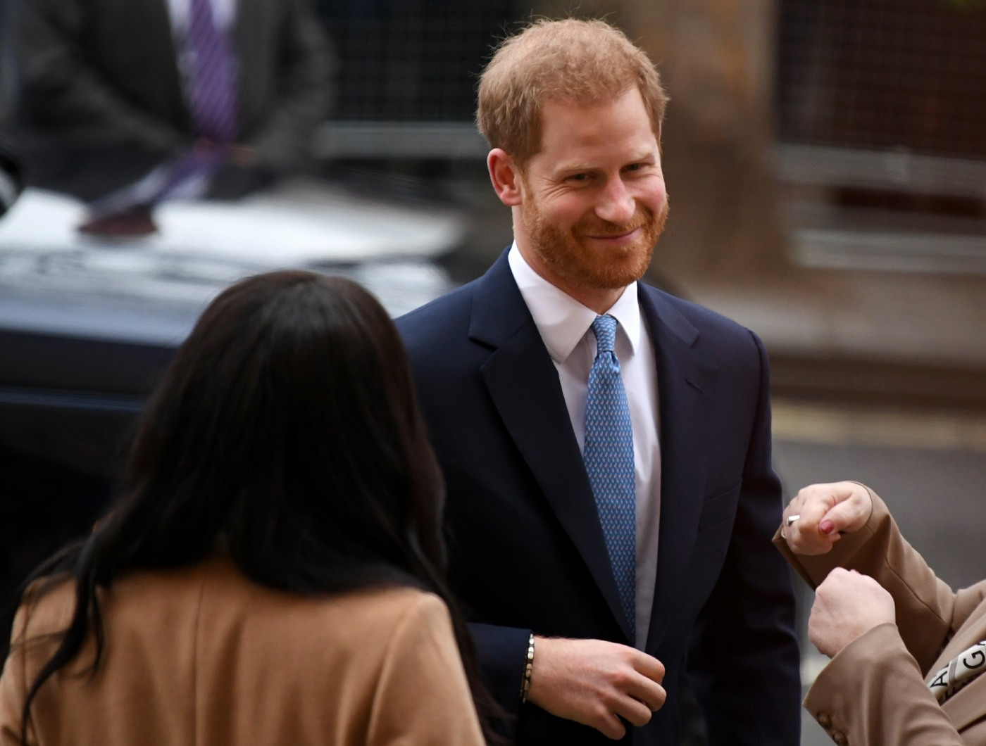 Britain's Meghan, Duchess of Sussex (L) and Britain's Prince Harry, Duke of Sussex (C) react as they arrive to visit Canada House, in London on January 7, 2020, in thanks for the warm Canadian hospitality and support they received during their recent stay
