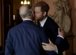 Britain's Prince Harry kisses and greets his father Prince Charles upon their separate arrival to attend a coral reef health and resilience meeting with speeches and a reception with delegates at Fishmongers Hall in London, Wednesday, Feb. 14, 2018. The e