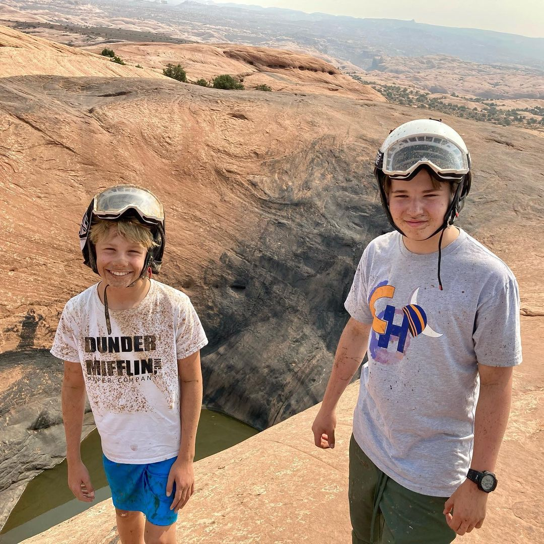 Julie Bowen's two sons, smiling and wearing t-shirts, shorts and helmets with goggles pushed up. They are dirty from an offroading trip in an open jeep