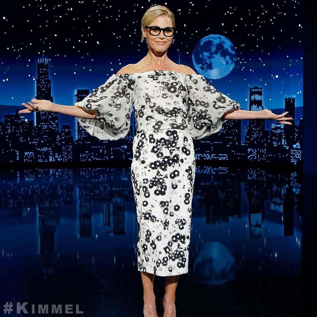 Julie Bowen on Kimmel via Instagram. She is wearing a white and black off the shoulder dress with balloon sleeves and her arms are outstretched