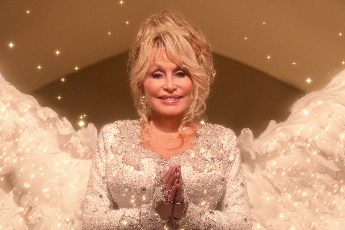 Dolly Parton dressed in a sequin angel-like outfit with wings and holding her hands in prayer. Photo is a still from Dolly's Netflix movie Christmas on the Square
