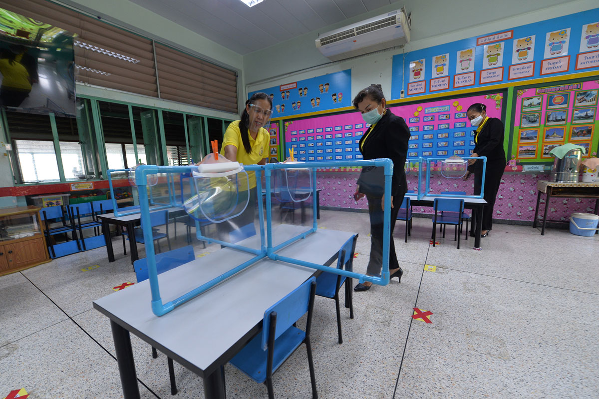Teachers in Thailand install shields in a classroom with small desks, June 2020