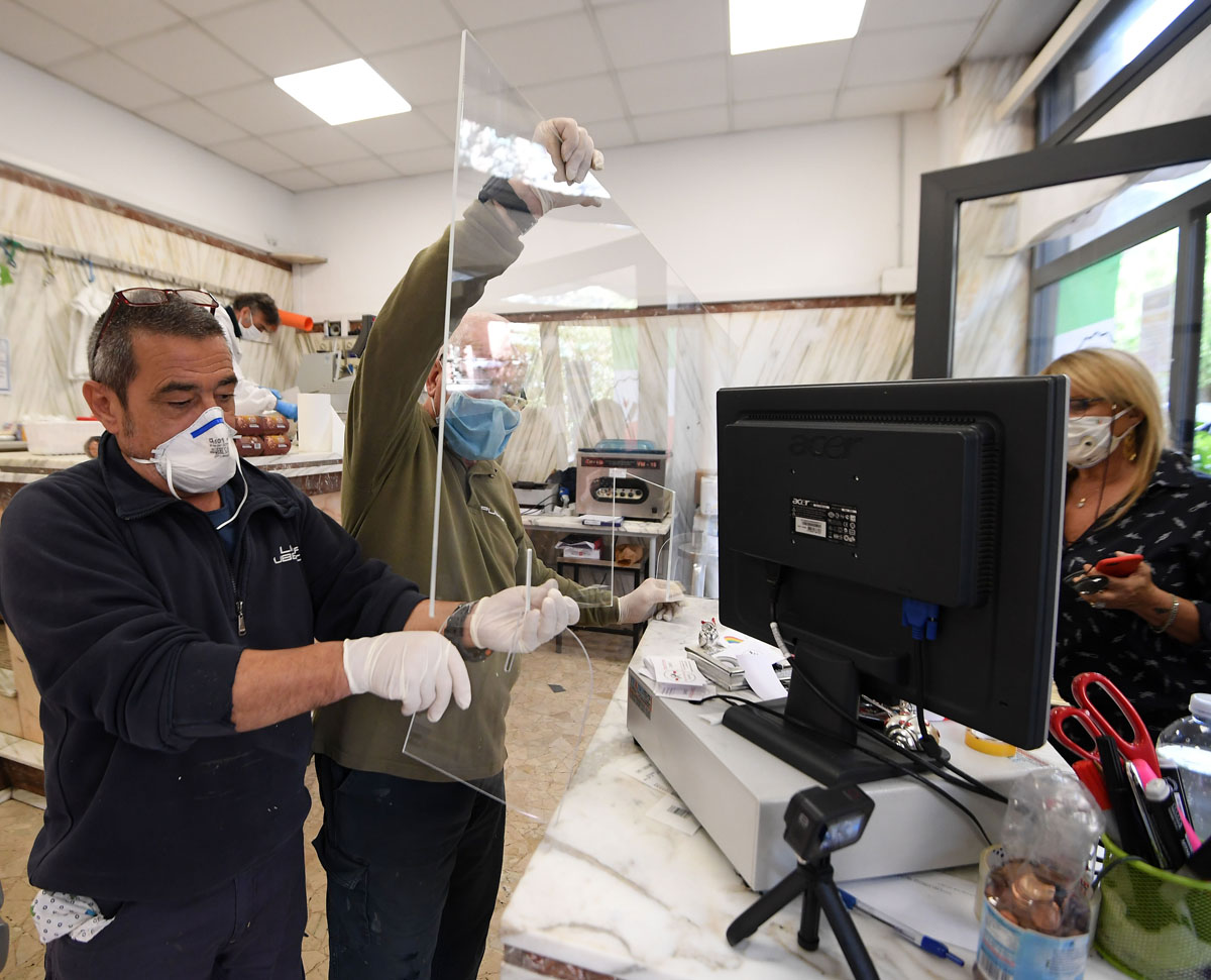 Workers install a plastic shield in a store in Rome, March 2020