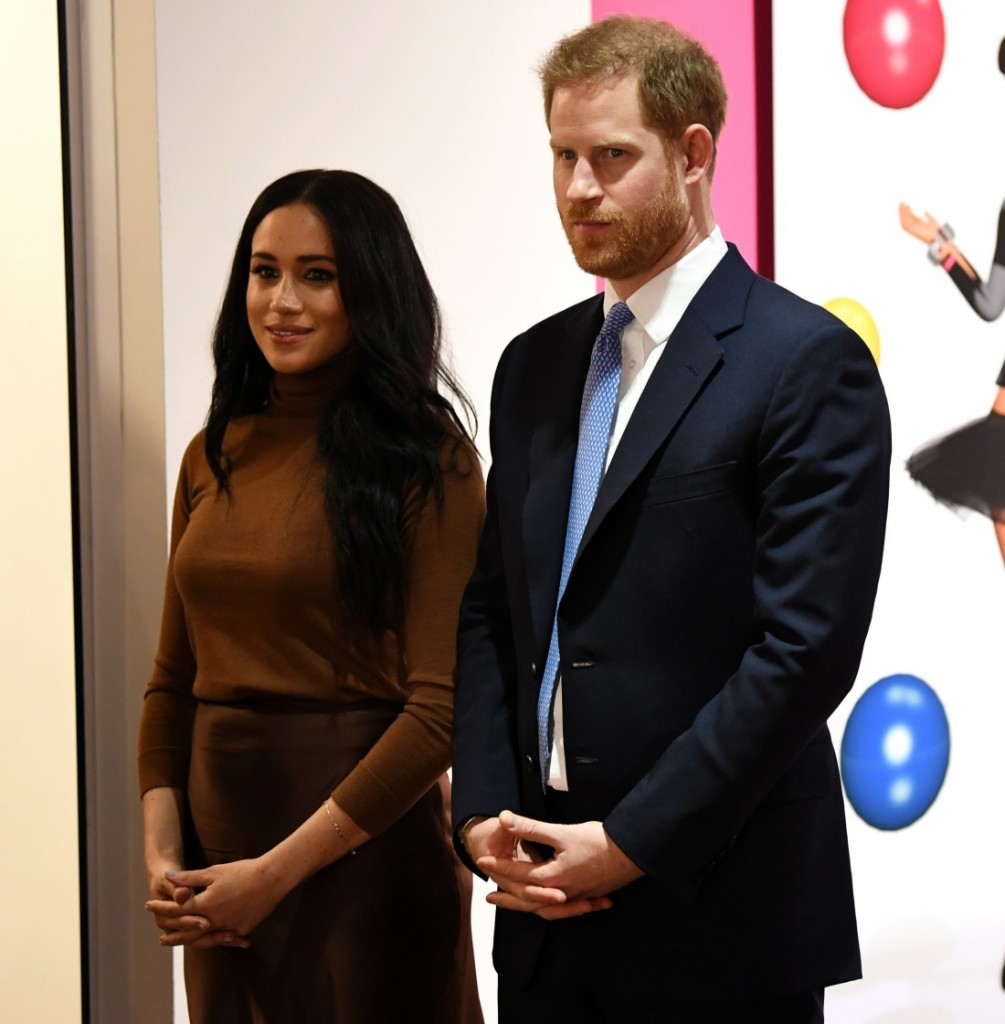 Britain's Prince Harry, Duke of Sussex and Meghan, Duchess of Sussex react as they are show a special exhibition of art by Indigenous Canadian artist, Skawennati, in the Canada Gallery during their visit to Canada House, in London on January 7, 2020, to gi