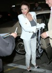 Joan Collins wears a tailored double breasted white suit and carries a Chanel scarf as she goes for dinner with husband Percy Gibson at Craig's in West Hollywood
